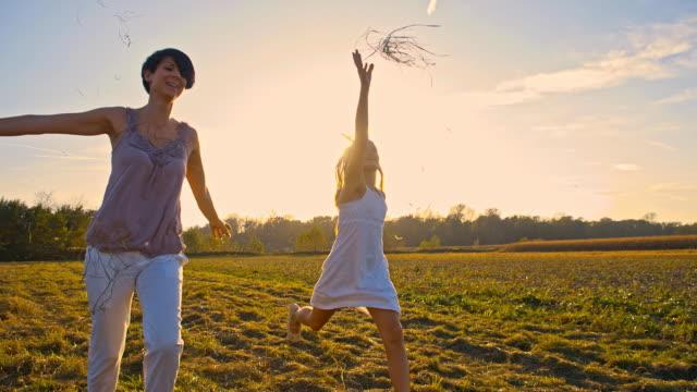 vidéos et rushes de slo missouri joyeuse mère et fille course dans prairie - robe d'été