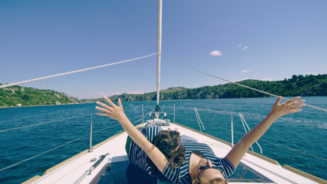 ds joyful mother enjoying the sailing while lying on a deck - punching the air stock videos & royalty-free footage