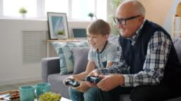 Joyful people old man and child playing video game talking having fun in apartment