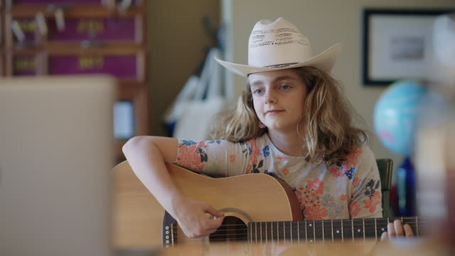 joyful pre-teen girl plays the guitar in front of laptop for her grandfather via video call - learning stock videos & royalty-free footage