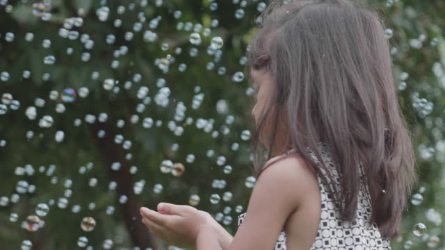 joyful siblings playing with soap bubbles at park. - bubble stock videos & royalty-free footage