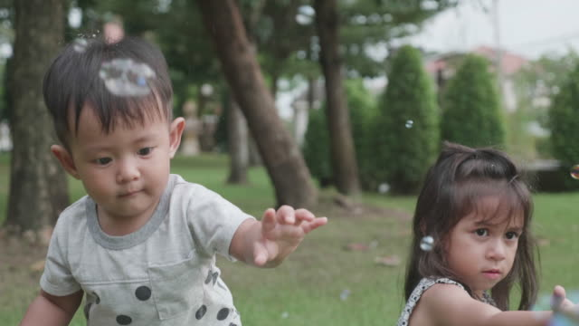 Joyful siblings playing with soap bubbles at park.