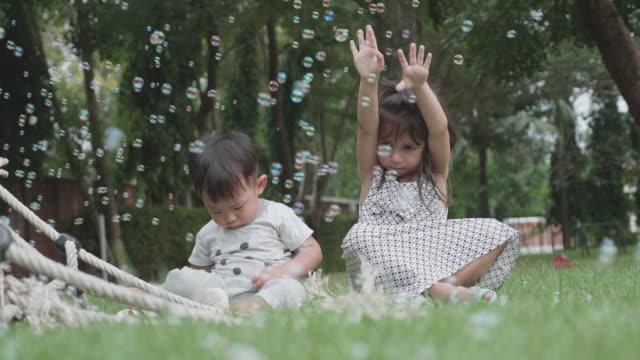 vídeos de stock, filmes e b-roll de alegres irmãos brincando com bolhas de sabão no parque. - bebês meninos
