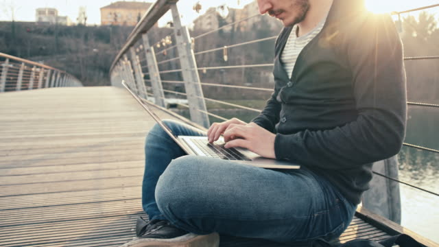 WS Joyful Student Using Laptop On Bridge