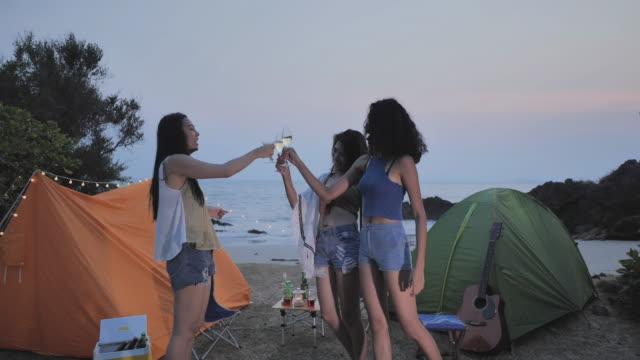 joyful tre tonåring flicka multi-etnisk grupp av vänner på en campng medan du njuter av drinkar och spela spel på stranden vid solnedgången. sydostasien och östra asien: kul på stranden - east asian ethnicity bildbanksvideor och videomaterial från bakom kulisserna
