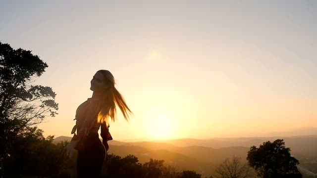 Vrolijke vrouw bij zonsondergang