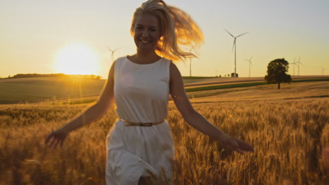 ms joyful woman caressing wheat plants while running in a field with wind turbines in the distance - adulto di mezza età video stock e b–roll