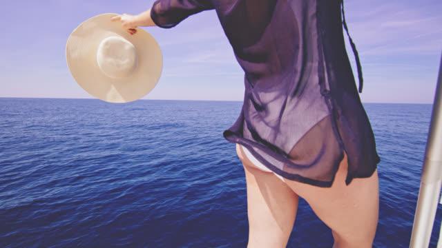 vídeos de stock e filmes b-roll de ws joyful woman in a cloak beach dress sailing on a sailboat - vela peça de embarcação