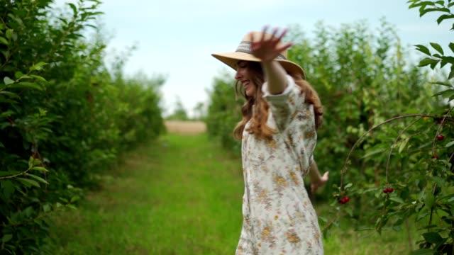 stockvideo's en b-roll-footage met blije vrouw in boomgaard - uitgestrekte armen