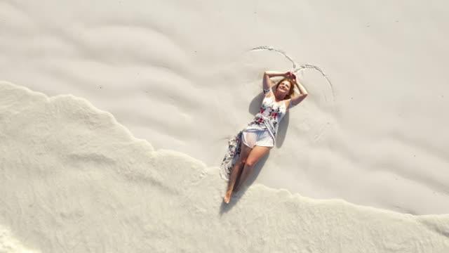 aerial joyful woman in sundress lying on the beach - sundress stock videos & royalty-free footage