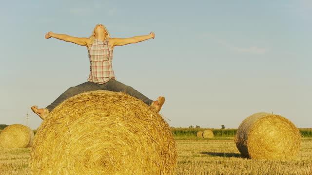 stockvideo's en b-roll-footage met hd dolly: joyful woman on hay bale - benen gespreid