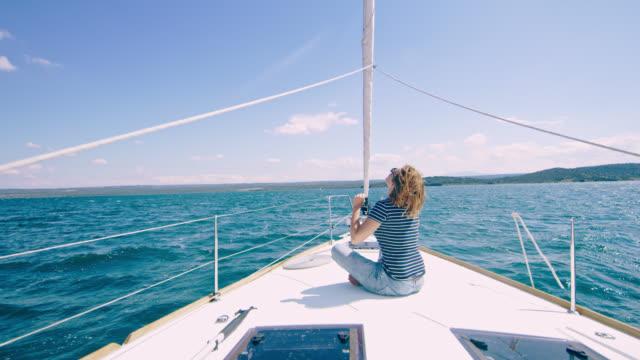 ws-fröhliche frau stanzen der luft auf einem deck eines segelbootes - spiritualität stock-videos und b-roll-filmmaterial