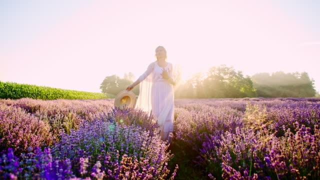 vidéos et rushes de slo mo joyeuse femme détente parmi les fleurs de lavande - chapeau
