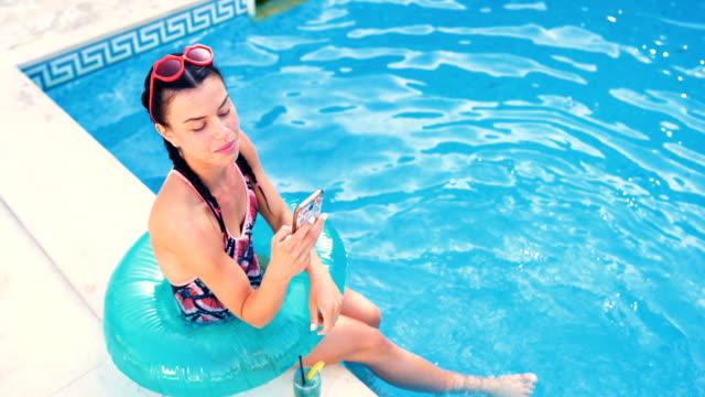 vidéos et rushes de femme joyeuse détente en bord de piscine - une seule jeune femme