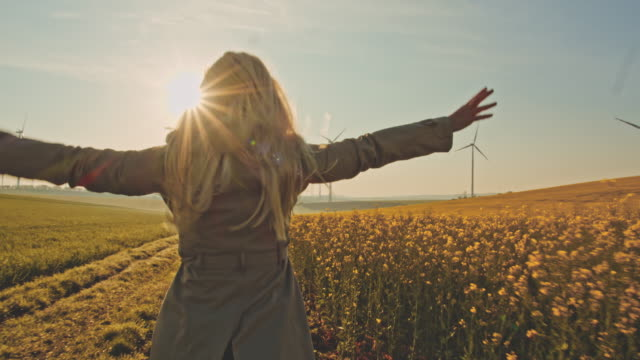 slo mo joyful woman running along field of canola with wind turbines in the distance - blonde hair stock videos & royalty-free footage