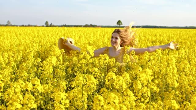 slo mo joyful woman running among blooming canola - sun hat stock videos & royalty-free footage