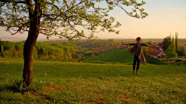 SLO MO 喜び女性スピニングの草地