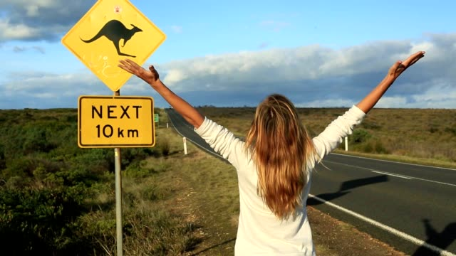 joyful woman stands arms outstretched near kangaroo crossing sign - road warning sign stock videos & royalty-free footage