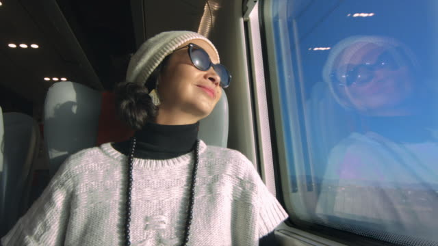 Joyful woman traveling by train enjoying the view and reading a magazine