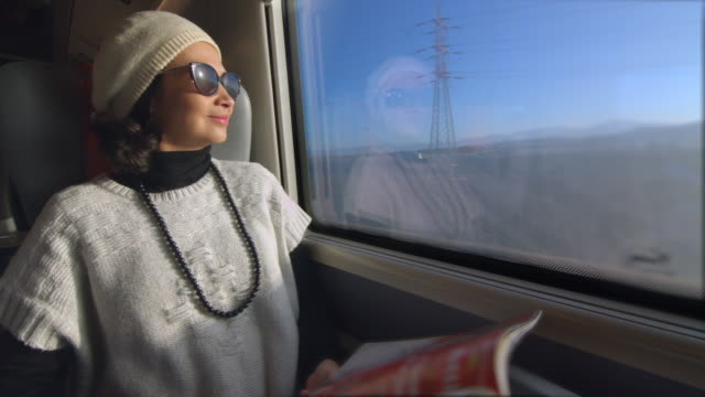 Joyful woman traveling by train enjoying the view through the window and reading a magazine