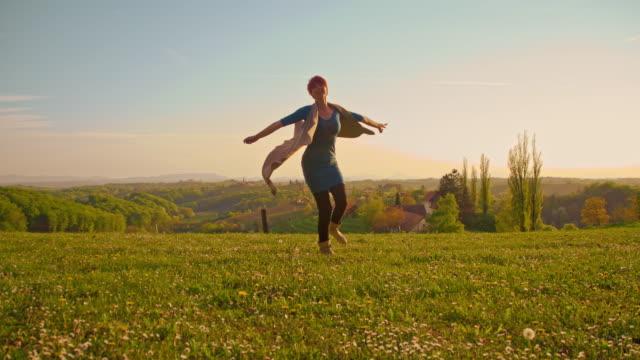 slo mo joyful woman twirling in spring meadow - prekmurje stock videos & royalty-free footage