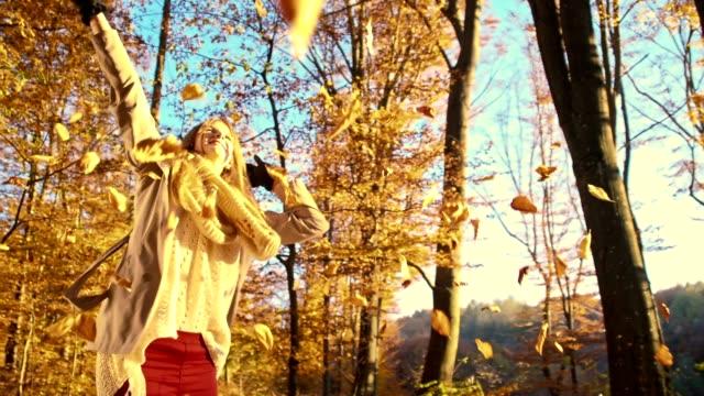 SLO MO Joyful woman twirling under falling autumn leaves