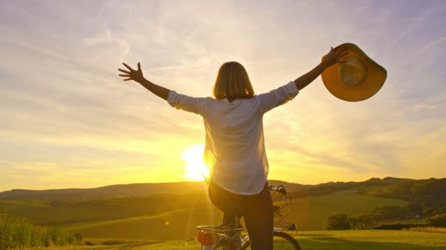 SLO-MO-fröhliche Frau mit ausgestreckten Armen einen Sonnenuntergang genießen