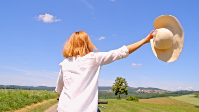 slo mo joyful woman with sunhat riding a bicycle - slovenia meadow stock videos & royalty-free footage