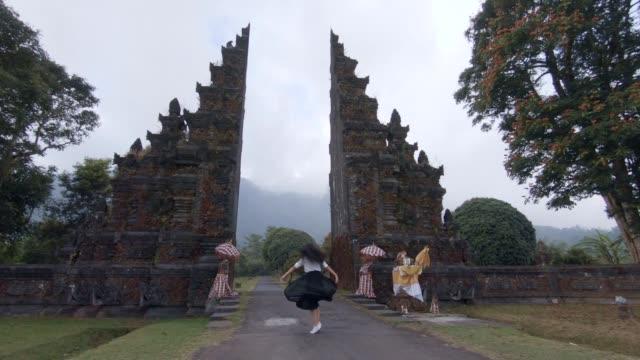 vídeos y material grabado en eventos de stock de alegre joven turista mujer bailando delante de puertas handara - cultura indonesia