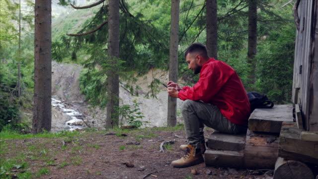 ウッドランドに携帯電話を使用してうれしそうな若い男