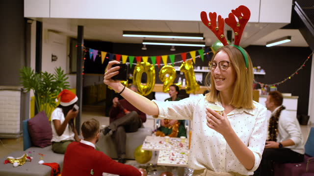 joyful young modern female entrepreneur taking a selfie during office party while wearing costume reindeer antlers - holiday event stock videos & royalty-free footage
