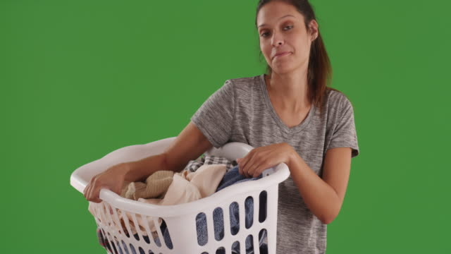 joyful young woman carrying laundry basket of dirty clothes on green screen - laundry basket stock videos and b-roll footage