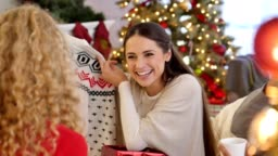 Joyful young woman opens a Christmas gift during ugly Christmas sweater gift exchange