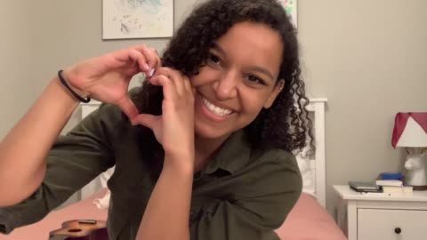 joyful young woman puts her hand over her heart, then forms a heart with her hands - webcam video stock e b–roll