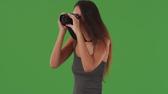 joyful young woman using dslr camera to take photos in front green screen wall - digital spegelreflexkamera bildbanksvideor och videomaterial från bakom kulisserna