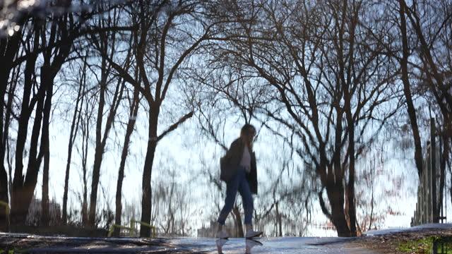 vidéos et rushes de jeune femme joyeuse marchant sur le bord d'une grande flaque d'eau - manteau et blouson d'hiver