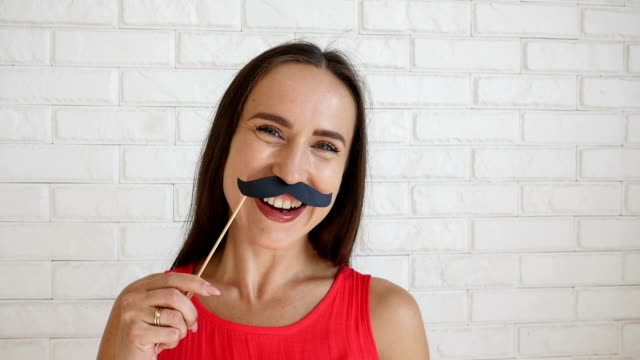 Joyful young†woman holding funny moustache on stick making funny faces