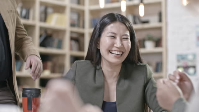 Joyous businesswomen laughing with coworkers