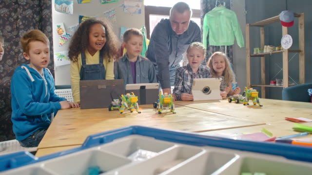 vídeos de stock, filmes e b-roll de joyous kids operating robot toys with assistance of male teacher - stem assunto