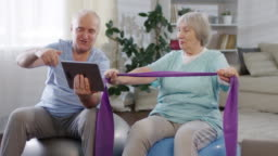 Joyous Senior Couple Using Tablet and Exercising at Home