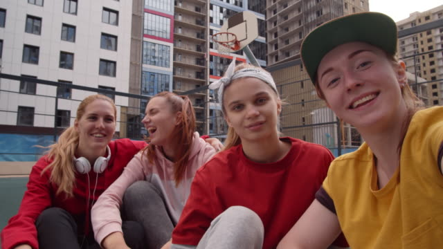 pov of joyous teenage girls taking selfie on outdoor urban court - sitting on ground stock videos & royalty-free footage