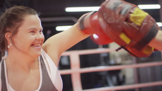 joyous woman with down syndrome punching focus pads while practicing boxing - disability stock-videos und b-roll-filmmaterial