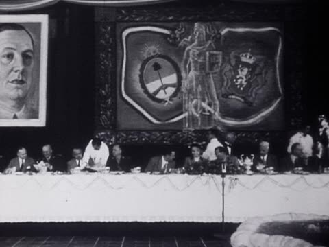 Juan and Eva Peron sit dining at a banquet