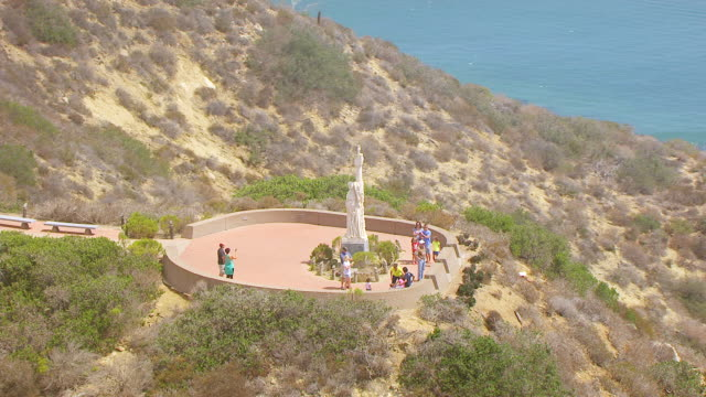 ws zo aerial pov orbit juan cabrillo statue and tourists with boats on the pacific ocean and hazy san diego in background / san diego, california, united states  - male likeness stock videos & royalty-free footage