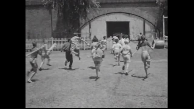 stockvideo's en b-roll-footage met jubilee oval glebe a group of teenagers and children get ready to play a game of softball / various shots of the kids playing boy with bare feet no... - blootvoets
