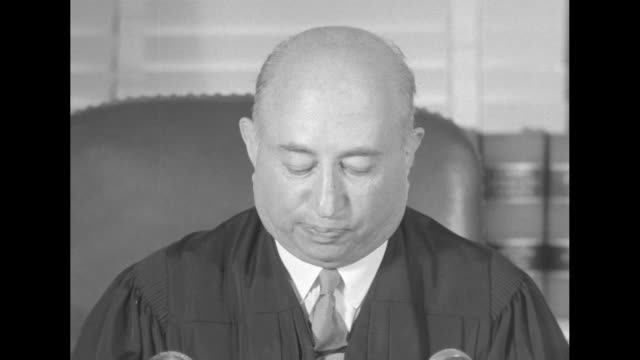 Judge Alexander Holtzoff sitting at his desk in office of courthouse of US District Court of District of Columbia reading his decision refusing to...