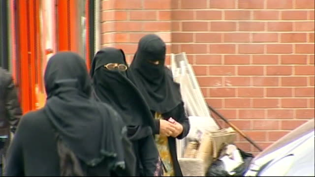 Judge rules woman must remove Muslim face veil when giving evidence T13071033 / TX Blackburn Two muslim women wearing headscarves along street Two...