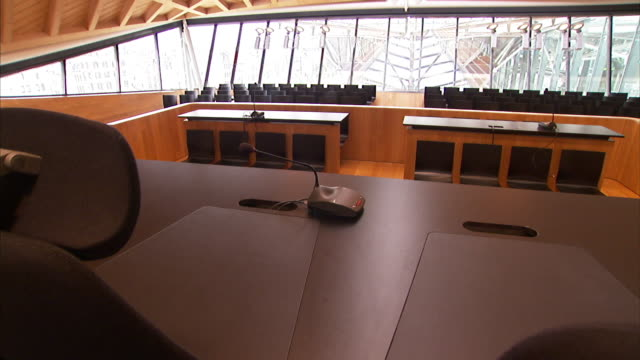 a judge's bench faces an empty courtroom. - gerichtssaal stock-videos und b-roll-filmmaterial