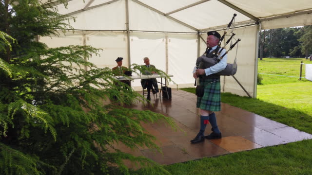 vidéos et rushes de judges watch as a solo piper competes at inveraray highland games on july 16, 2019 in inverarary, scotland.the games celebrate scottish culture and... - scottish culture