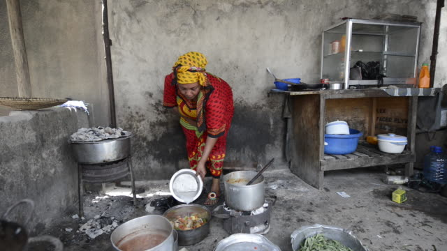 brac project, judith msechu cooking and running small street restaurant in temeke district. makes about $120 a month. - ブラック島点の映像素材/bロール